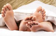 Image of two pairs of bare male and female feet seen from under blanket Stock Photos