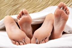 image of two pairs of bare male and female feet during sleep - stock photo