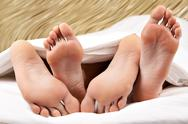 Image of two pairs of bare male and female feet during sleep Stock Photos
