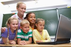 portrait of pupils looking at the laptop with teacher near by - stock photo