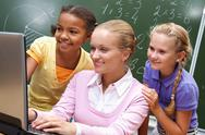 Stock Photo of portrait of two girls and teacher looking at the laptop in classroom