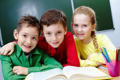 Portrait of two guys and girl sitting in classroom with open book near by Stock Photos