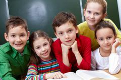 Portrait of five pupils sitting in classroom with open book near by Stock Photos