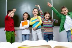 portrait of five pupils having fun in classroom - stock photo