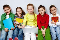 portrait of five pupils looking at camera while sitting on the floor - stock photo