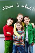 group of  happy classmates together by whiteboard with text welcome to school - stock photo