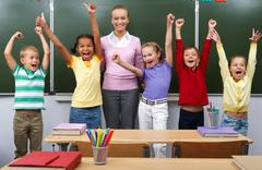 Line of cute schoolchildren raising arms with their teacher in the middle Stock Photos