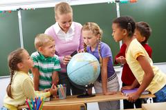 portrait of pupils looking at globe while listening to teacher during geography - stock photo