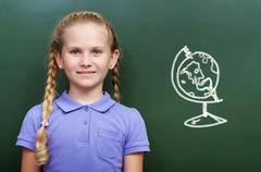 portrait of smart girl by the blackboard looking at camera - stock photo