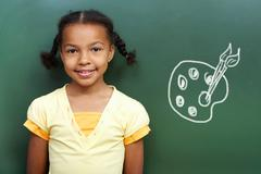 portrait of cute girl by the blackboard looking at camera - stock photo