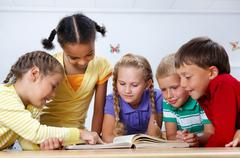 Portrait of pupils looking at page of encyclopaedia at reading lesson Stock Photos