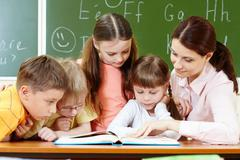 portrait of smart schoolchildren and their teacher reading book in classroom - stock photo