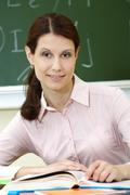 Stock Photo of portrait of smart teacher at workplace looking at camera
