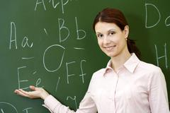 portrait of smart teacher pointing at letters on blackboard and looking at camer - stock photo