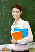 portrait of smart teacher with books by the blackboard looking at camera - stock photo