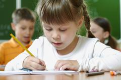 portrait of smart schoolgirl drawing at lesson in classroom - stock photo