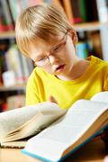 Portrait of cute schoolkid reading books in the library Stock Photos