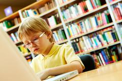 Portrait of serious schoolkid working with laptop in the library Stock Photos