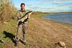 Fishing man with big zander fish Stock Photos