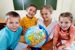 portrait of cute schoolchildren and teacher with globe looking at camera - stock photo