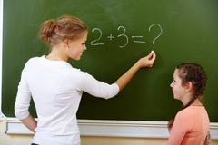 photo of teacher writing sum on blackboard and looking at pretty pupil near by - stock photo