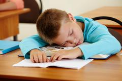 Cute schoolboy lying on book and sleeping in class during lesson Stock Photos