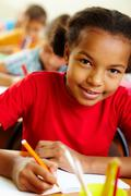Stock Photo of portrait of lovely girl drawing with crayons at lesson