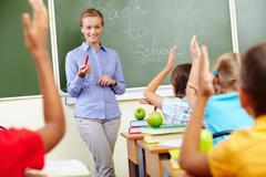 Portrait of smart teacher by blackboard looking at schoolkids in classroom Stock Photos