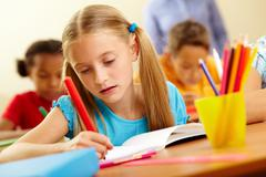 Stock Photo of portrait of lovely girl drawing with colorful pencils at lesson