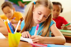 Portrait of lovely girl drawing with colorful pencils at lesson Stock Photos