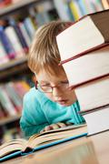 portrait of cute boy reading book in library - stock photo