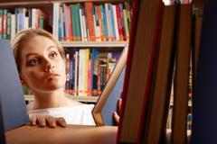 portrait of clever student looking for a book in college library - stock photo