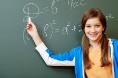 Confident student pointing at formula on blackboard during algebra lesson Stock Photos