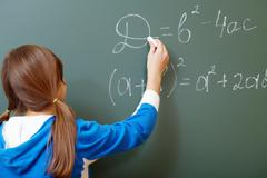 confident student pointing at formula on blackboard during algebra lesson - stock photo