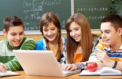 portrait of clever students sitting at lesson and looking at laptop monitor - stock photo