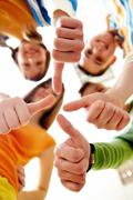 below angle of happy teens showing thumbs up - stock photo