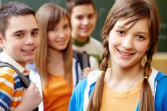 confident student looking at camera with her friends behind - stock photo