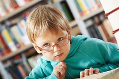 portrait of clever boy thinking in library - stock photo