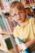 Portrait of clever boy holding book and looking at camera in library Stock Photos