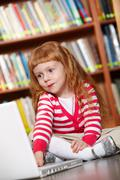 portrait of smart girl sitting on the floor in library in front laptop - stock photo