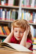 Portrait of smart girl reading book in library Stock Photos