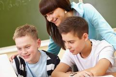 Portrait of two guys and girl being busy during lesson Stock Photos