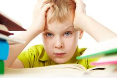 portrait of a little boy among books - stock photo