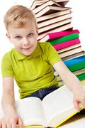portrait of a boy sitting with a book at the heap of books - stock photo
