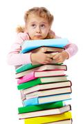 Portrait of a little girl trying to carry a huge heap of books Stock Photos