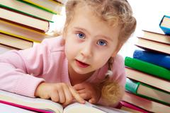 Portrait of a little girl among books Stock Photos