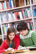 portrait of teenage girl reading book with her classmate near by - stock photo