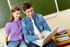 Portrait of guy and girl being busy during lesson Stock Photos