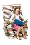 Portrait of diligent pupil sitting on pile of books and reading one of them Stock Photos