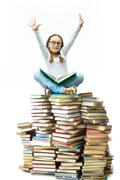 Portrait of cute girl sitting on pile of books with raised arms Stock Photos